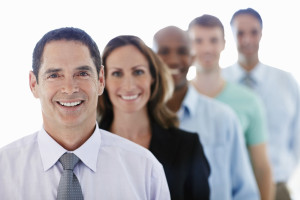 Portrait of middle aged business man smiling with his colleagues over white background